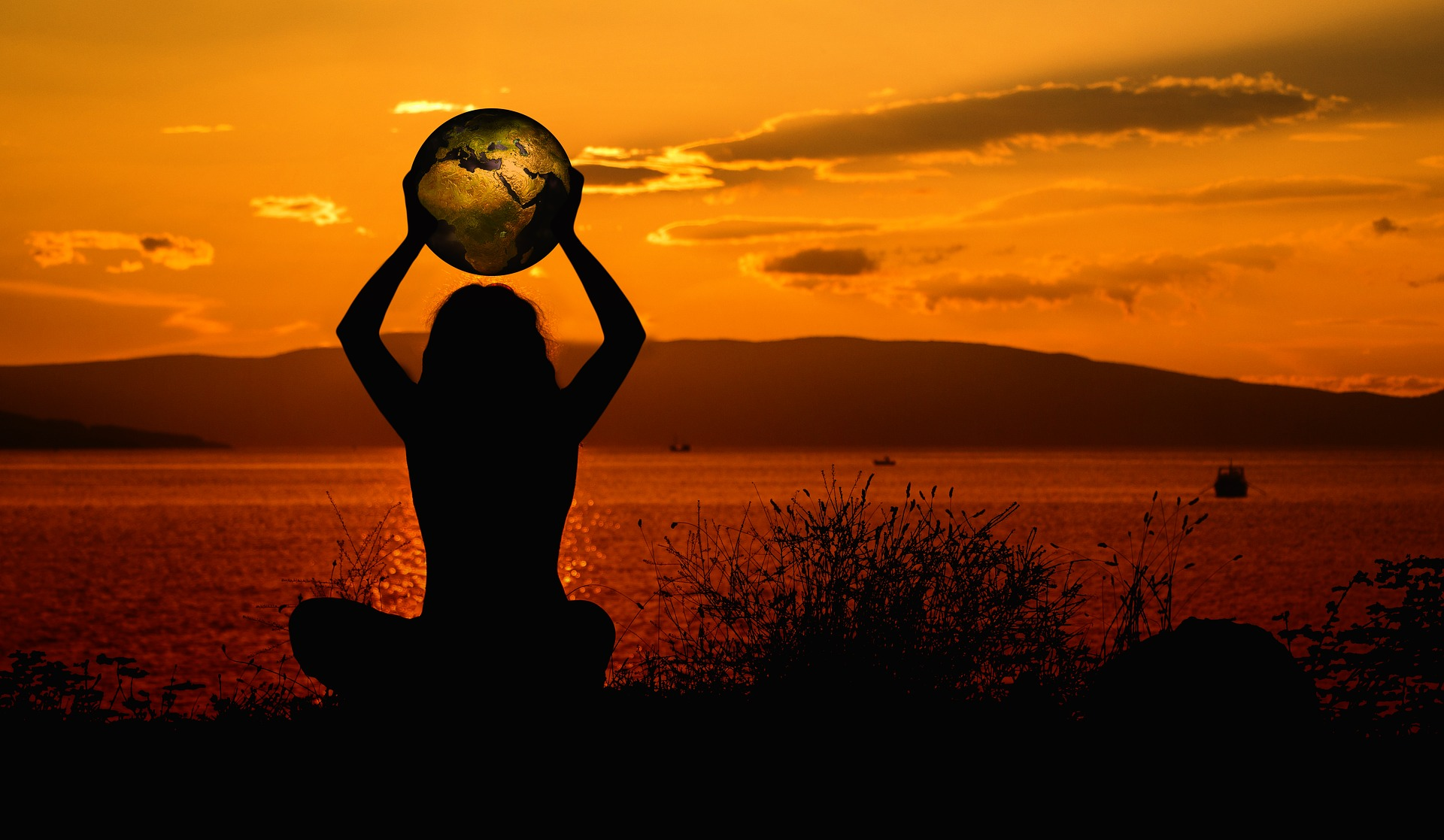 Person holding an Earth sitting in the sunset